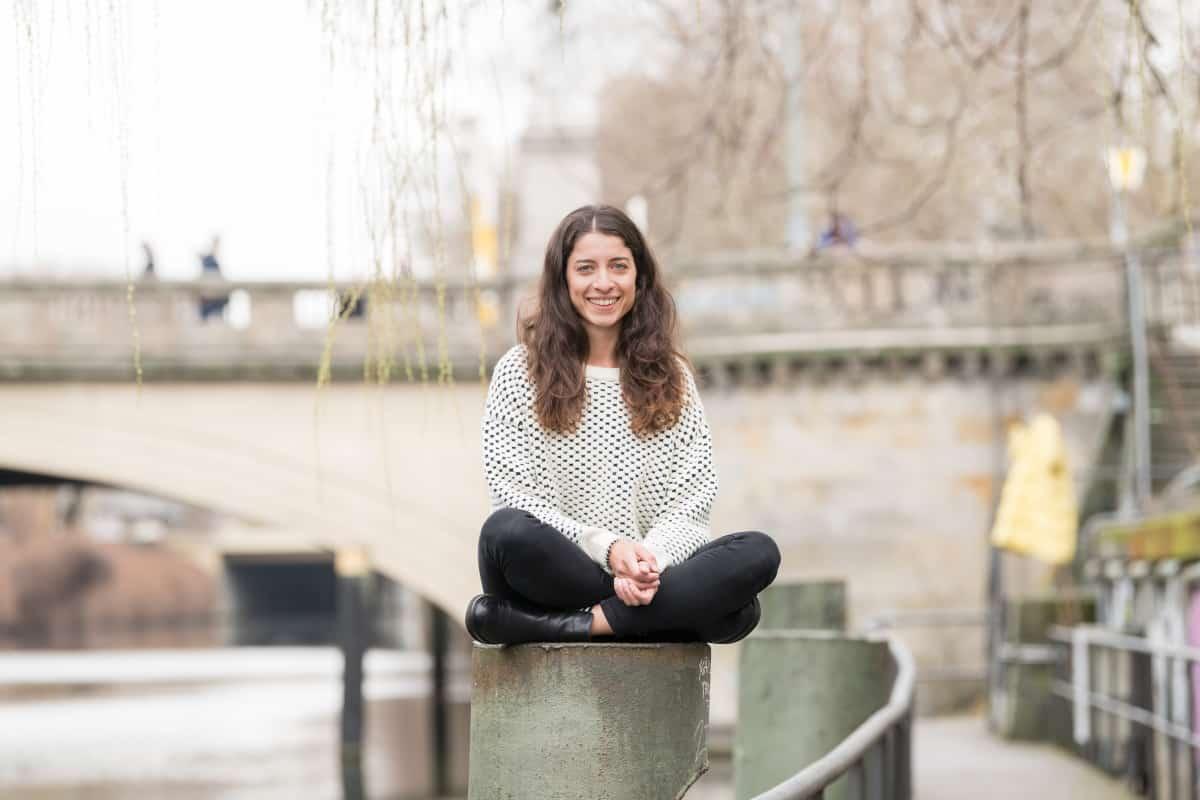 Sara sitzt vor Brücke